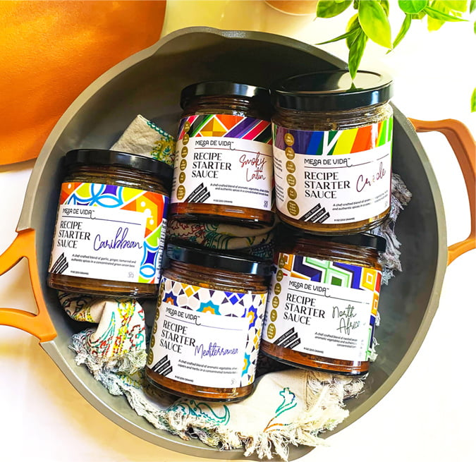 Mesa de Vida Globally inspired healthy cooking sauces and healthy pantry staples lined up. Caribbean, Creole, North African, Mediterranean and Smoky Latin flavors