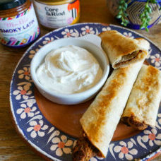 Plate of crispy oven-baked taquitos, a side of sour cream on a colorful Mexican plate